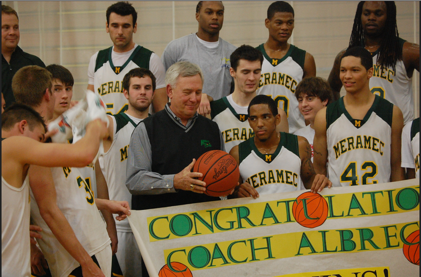 Coach Albrecht (fifth from the left) holds a congratulatory banner presented by the Magic basketball team after his 700th win in 2011. | DAVID KLOECKENER