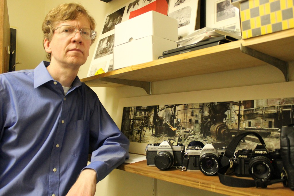 David Hanlon poses with some of his favorite cameras, in front of a picture one of his students took. Before teaching photography at Meramec for the past 12 years, Hanlon taught part time at STLCC-Florissant Valley for 12 years. His nearly two-and-a-half decade experience behind the lens allowed Hanlon to be invited by the NPA (Nanjing Photography Association) as one of ten photographers from the St. Louis area to travel to China for a 12 day trip. PHOTO | DALILA KAHVEDZIC