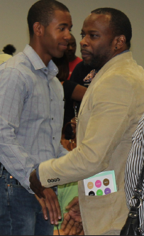 """Above: two men shake hands at the Ferguson community meeting on Wednesday, Sept. 24. The meeting allowed community members to express their frustration with how the Michael Brown case is being handled by the Department of Justice. Left: The mantra """"Hands up don't shoot"""" was the theme of the meeting for the outraged Ferguson residents.  PHOTO   SABREE BLACKMON"""