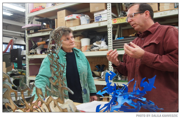 Joe Chesla instructs student, Mary Anne Nye, on what steps to take next with her sculpture.